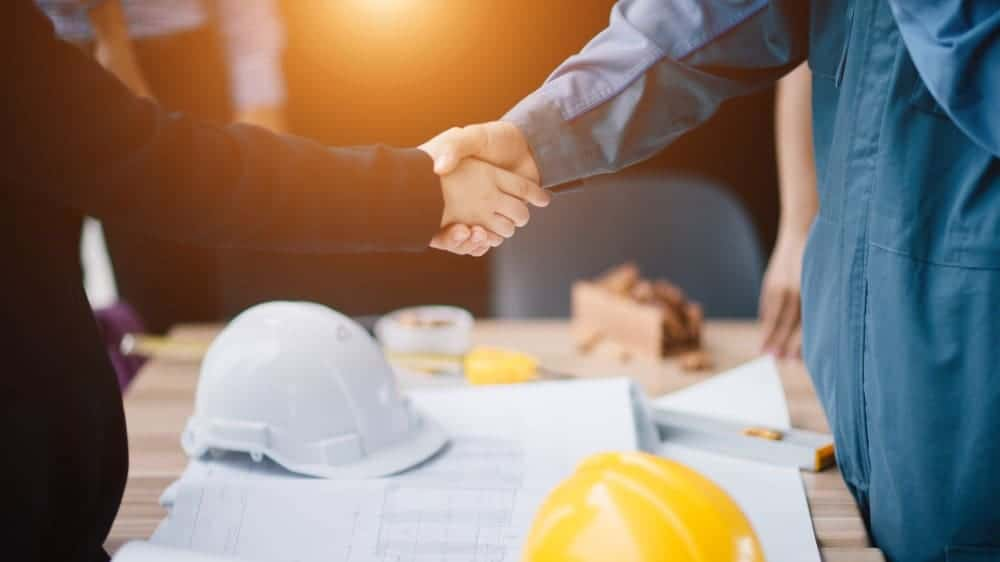 Businessman and engineer handshake closing a deal in construction site